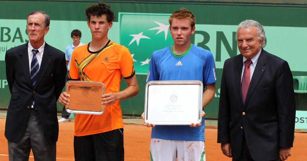 Dominic Thiem with the finalist trophy from the 2011 Boys' French Open, alongside winner Bjorn Fratangelo