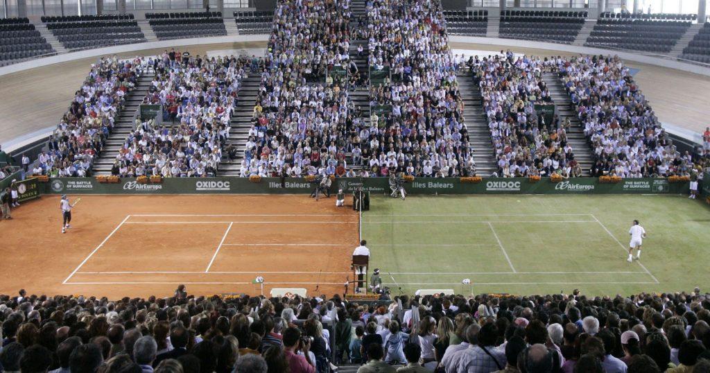 """Federer et Nadal pendant l'exhibition """"La bataille des surfaces"""" en 2007. Le court avait été divisé en deux parties, l'une en gazon, l'autre en terre battue."""