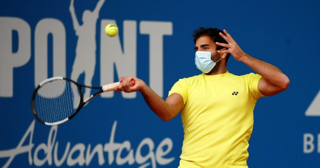 Hassan wearing a mask during warm-up at Exo Tennis.